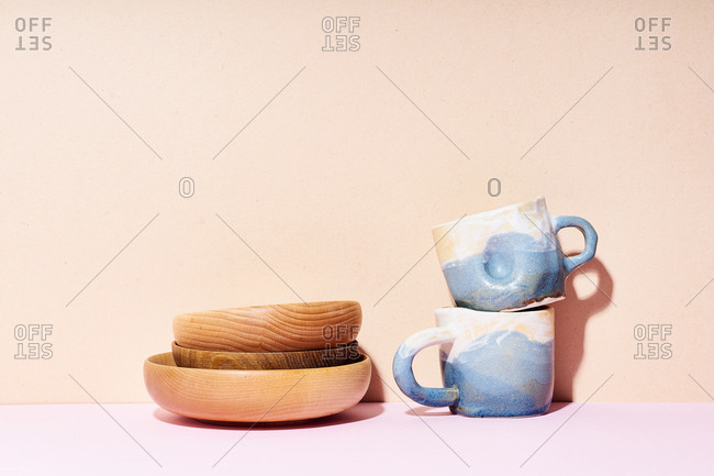 Still life with handmade ceramic cups and wooden bowls on bright studio