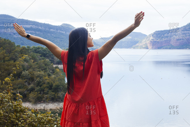 Back view of dreamy female tourist in summer dress standing with outstretched arms on hill near lake in highlands and enjoying vacation