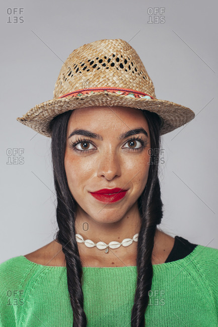 Attractive young ethnic female with red lips and pigtails wearing stylish straw hat and necklace looking at camera against gray background