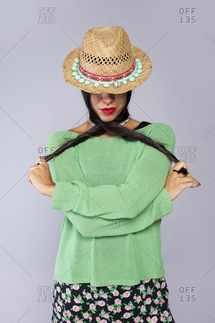 Confident young long haired brunette with red lips wearing colorful clothes and trendy straw hat