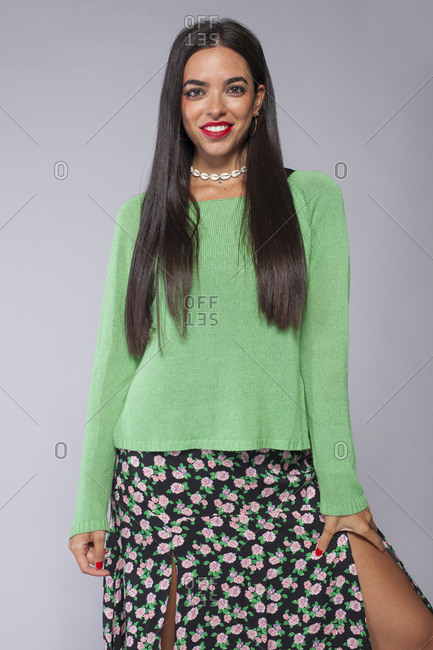 Stylish confident young ethnic brunette with long hair and red lips wearing green knitted blouse