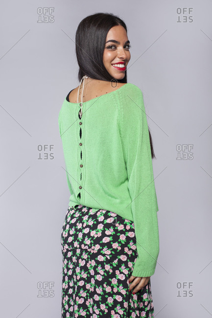 Side view of stylish cheerful young ethnic brunette with long hair and red lips wearing green knitted blouse