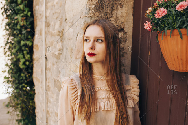 Dreamy female with red lips and in stylish outfit standing near old building in historic city and looking away