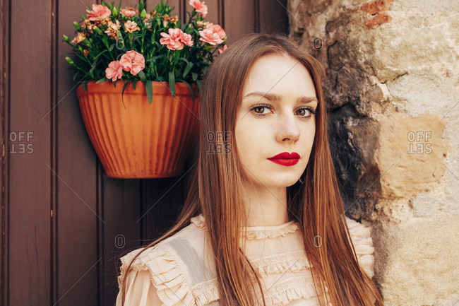 Dreamy female with red lips and in stylish outfit standing near old building in historic city and looking at camera