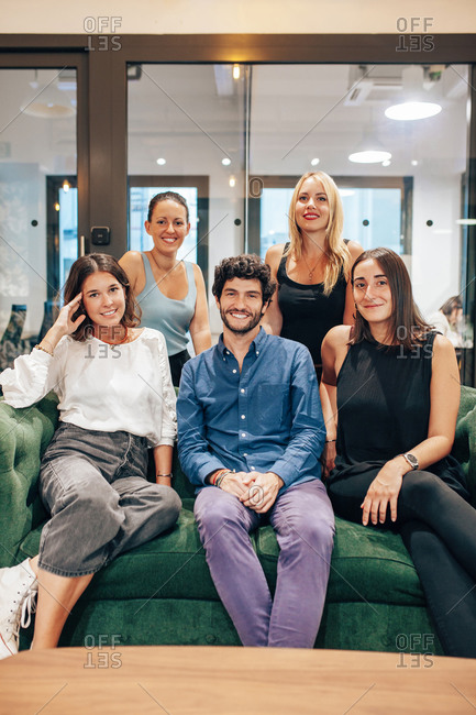 Group of optimistic young coworkers in casual outfits gathering together on comfortable sofa and looking at camera while having meeting in contemporary workspace