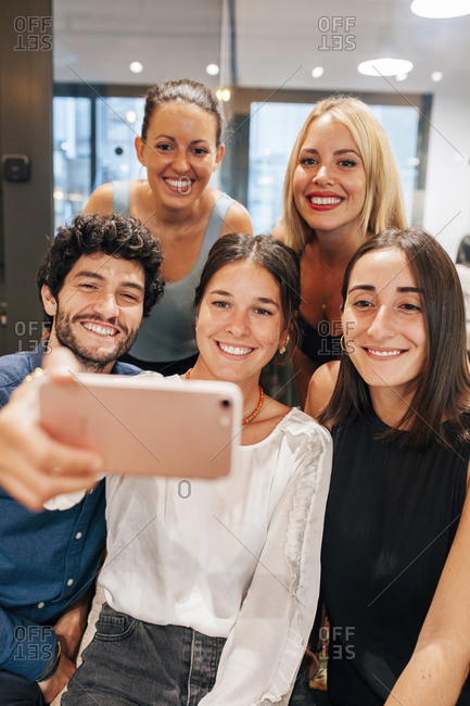 Young creative startup team smiling and taking selfie on mobile phone while gathering together in modern workspace