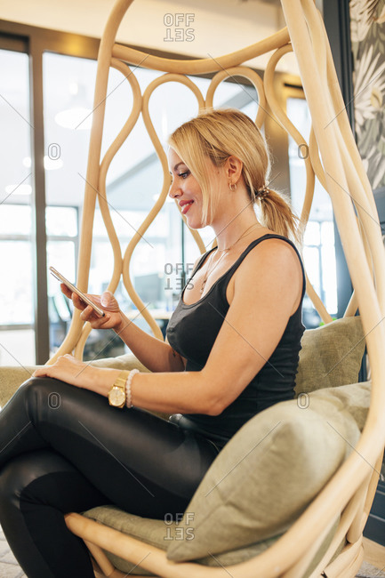 Confident satisfied young female entrepreneur in trendy informal outfit sitting in hanging wicker chair in creative workspace on mobile phone