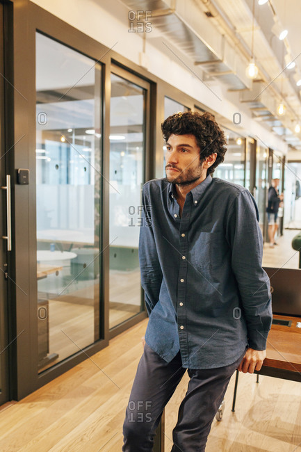 Young bearded male entrepreneur in casual outfit standing in corridor of contemporary business center and looking away pensively