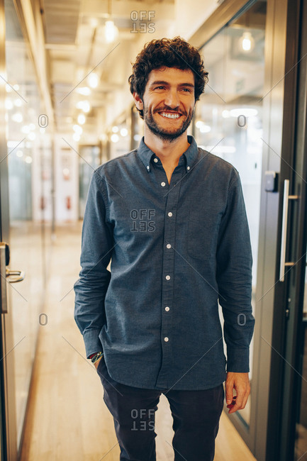 Content successful young man in casual outfit standing in hallway of modern office building and smiling happily