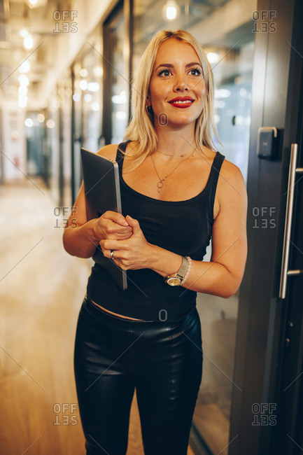 Smiling young blond female designer in stylish informal wear holding laptop while standing in corridor of contemporary office building