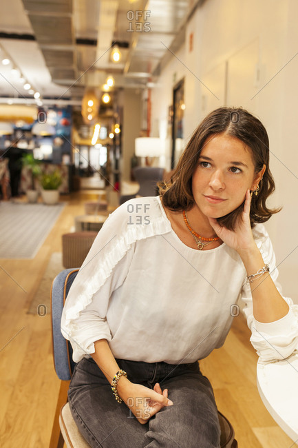Positive young female in casual outfit sitting at table looking away in modern workspace