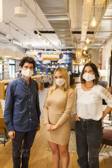 Group of modern diverse young coworkers in informal outfits and protective masks looking at camera while standing together against blurred background of contemporary workspace