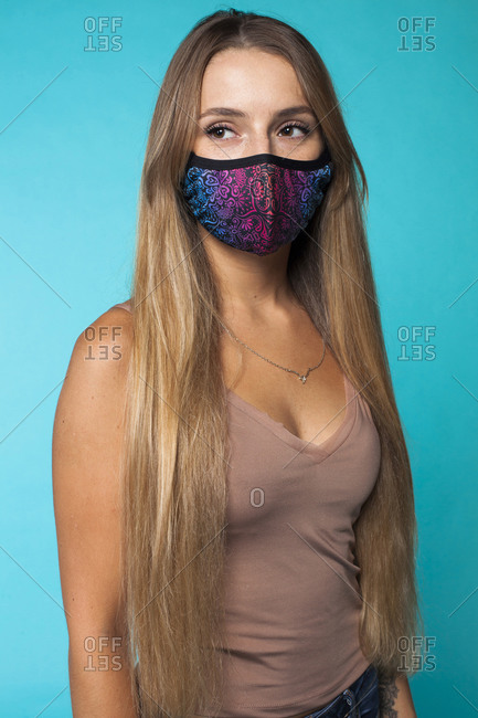 Positive young long haired female model in fashionable colorful protective mask against blue background