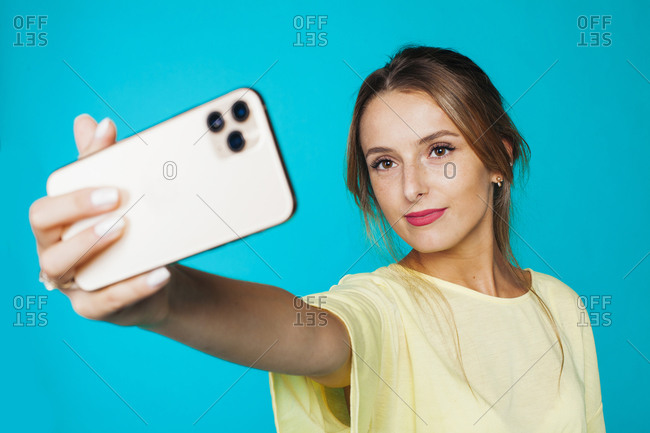 Cheerful coquettish millennial female in casual outfit and with beautiful makeup capturing selfie on mobile phone while standing against bright blue backdrop