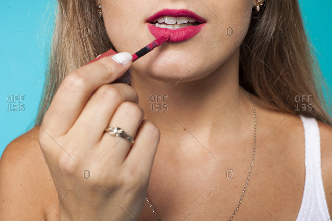 Closeup of crop anonymous female applying bright pink liquid lipstick against blue background