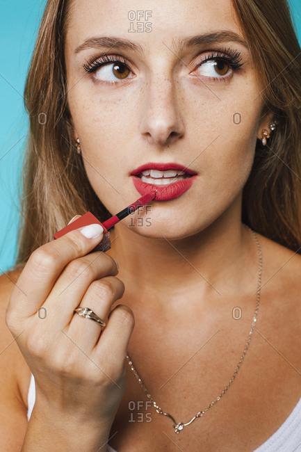 Closeup of crop female applying bright pink liquid lipstick against blue background
