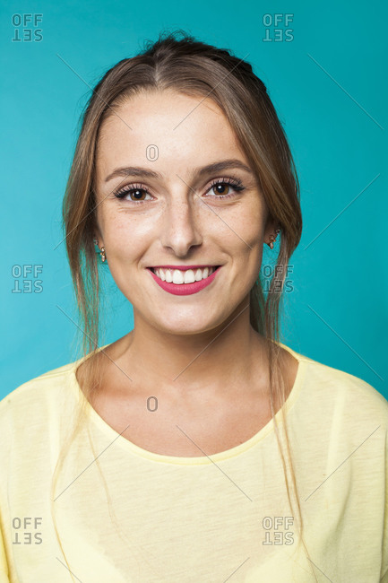Cheerful attractive female with freckles and casual makeup looking at camera against blue background