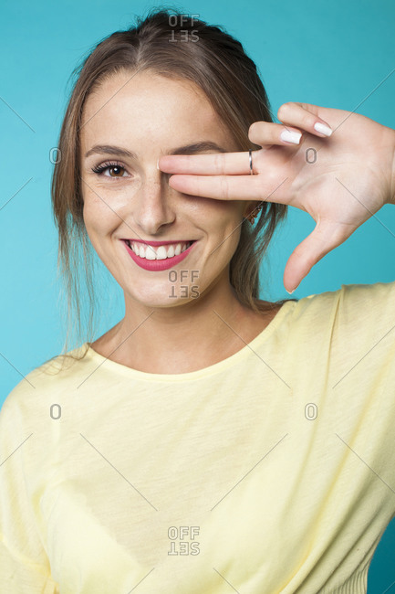 Happy young freckled female model in casual outfit and with perfect makeup keeping fingers near eye and looking at camera against blue background