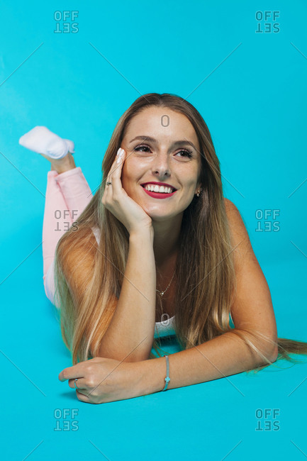 Full length of cheerful dreamy millennial female in casual outfit leaning chin on hand while lying in bright blue studio