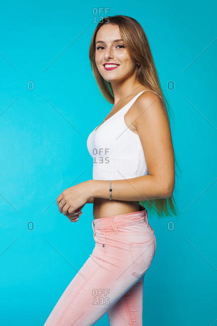 Modern millennial slim female model wearing white cropped tank top and pink skinny jeans smiling and looking at camera against blue background