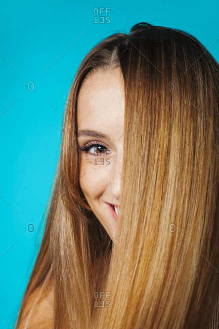 Charming positive young female with long straight fair hair covering half of face looking at camera against blue background