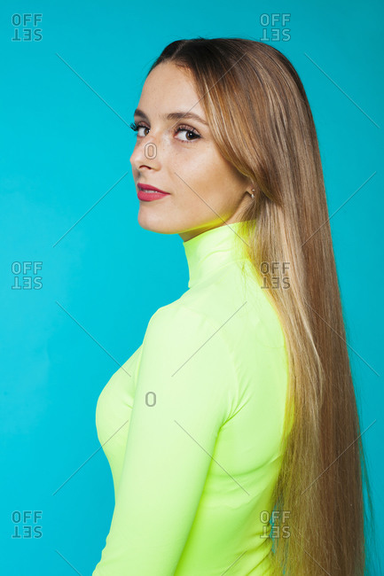 Side view of charming gentle long haired blondie with beautiful makeup wearing bright green turtleneck looking at camera over shoulder against blue background