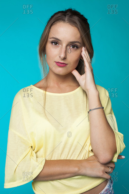 Calm confident young female model with makeup wearing trendy casual blouse touching face and looking at camera against blue background