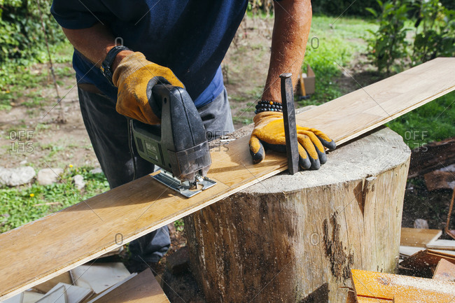 Crop unrecognizable male woodworker cutting wooden plank with electric device while working in countryside