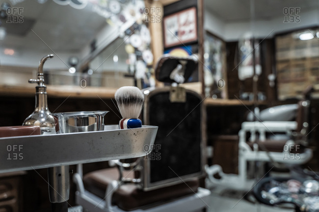 Set of vintage barber tools and accessories including metal spray bottle with brush for shaving and razors in stylish barbershop