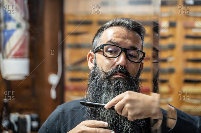 Stylish middle aged male in eyeglasses with mustache looking at mirror and combing long beard while sitting in barbershop