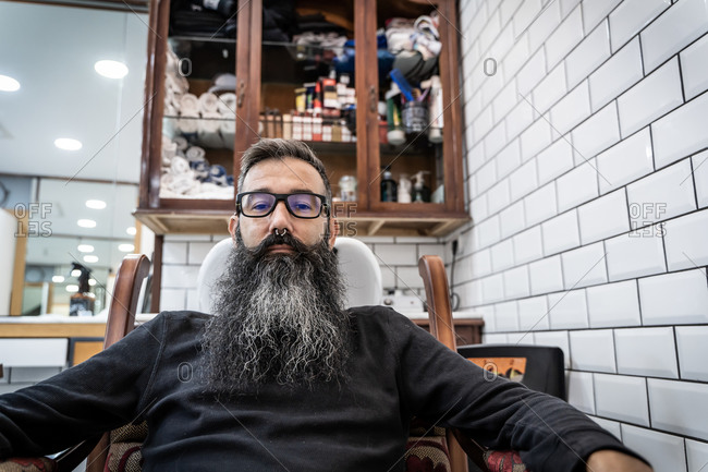 Serious middle aged male client in eyeglasses with piercing and long beard and mustache sitting in chair in barbershop looking at camera