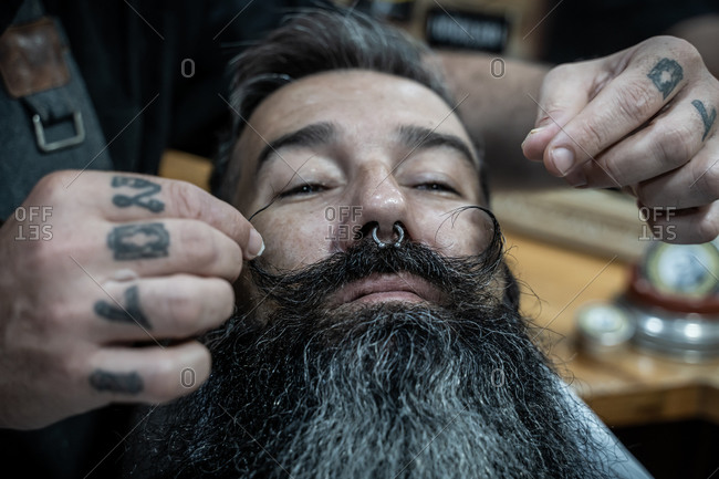 Crop anonymous barber with tattooed fingers styling mustache of stylish hipster bearded customer in barbershop