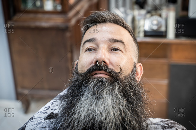 Serious middle aged male client with piercing and long beard and mustache sitting in chair in barbershop looking away