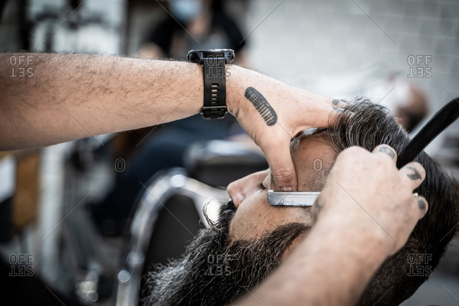 Side view of cropped unrecognizable tattooed barber with razor finishing haircut of mature brutal bearded male consumer in barbershop