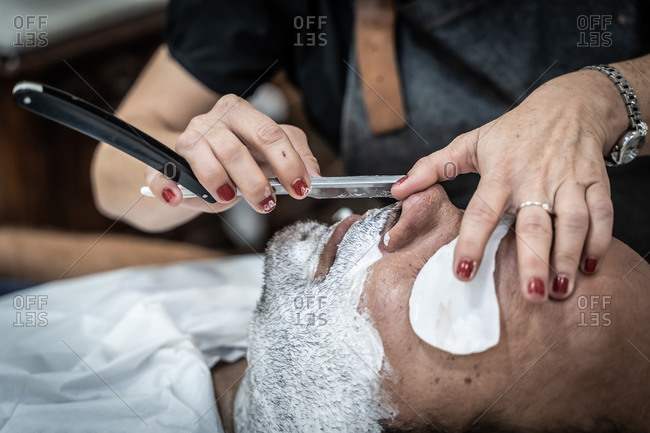 Crop unrecognizable female master with razor shaving beard and mustache of relaxed client with foam on face in barbershop