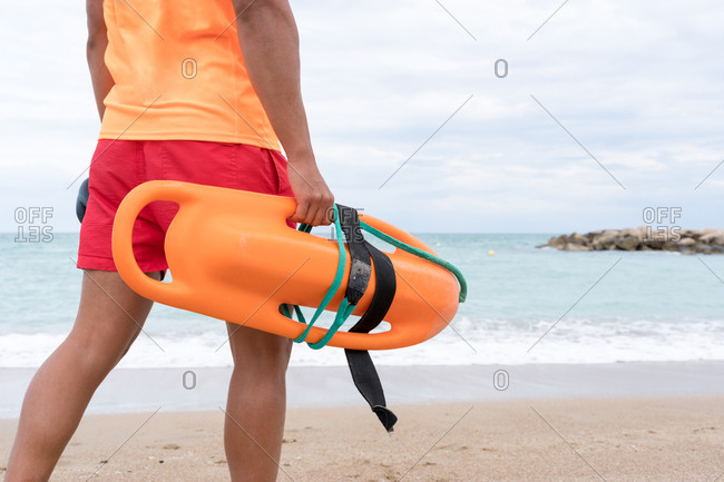 Back view of crop anonymous man in bright wear strolling on sandy shore with torpedo rescue buoy
