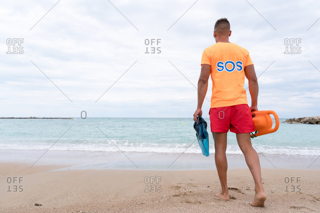 Back view of unrecognizable stylish male employee with torpedo rescue buoy strolling on foamy sea under cloudy sky