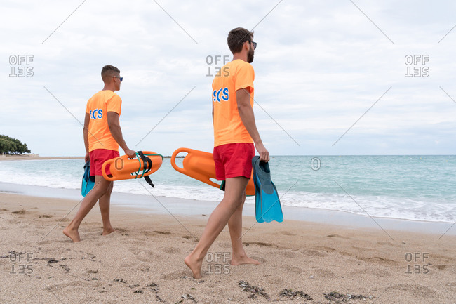 Back view of anonymous fit male partners in sunglasses and uniform strolling on sandy ocean coast with torpedo rescue buoys and flippers