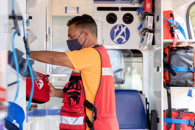 Side view of unrecognizable male employee in bright uniform and face mask taking first aid kit in ambulance