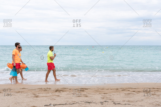 Side view of fit male partners in sunglasses and uniform strolling on sandy ocean coast with torpedo rescue buoys and flippers