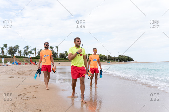 Male employees in bright wear with walkie talkie radio and flippers standing on wavy sea while looking away