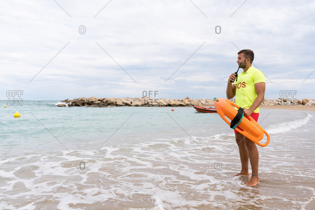 Young male employee in colorful outfit with torpedo life saver and walkie talkie radio standing on sandy sea shore while looking away
