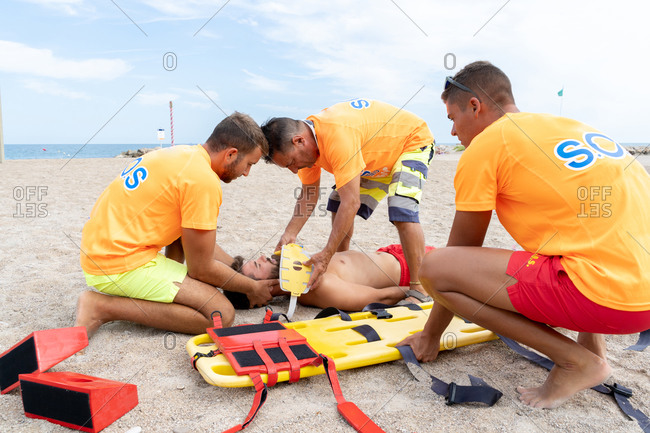 Side view of male lifeguards in uniform helping patient lying on sandy seashore near stretcher