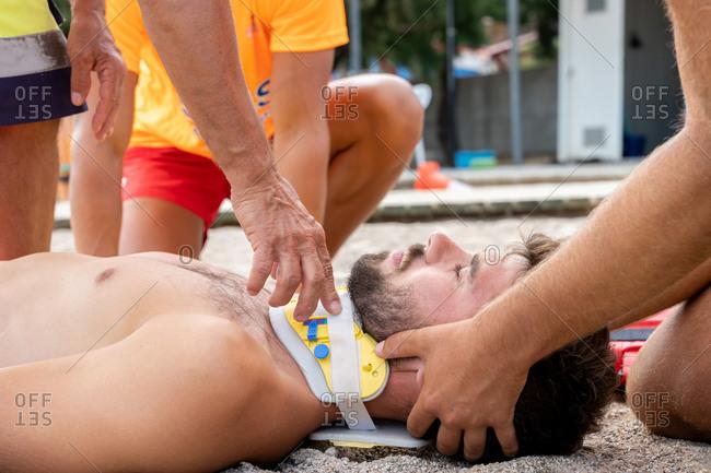 Crop unrecognizable lifeguard in uniform helping bearded patient in emergency head block during practice at work