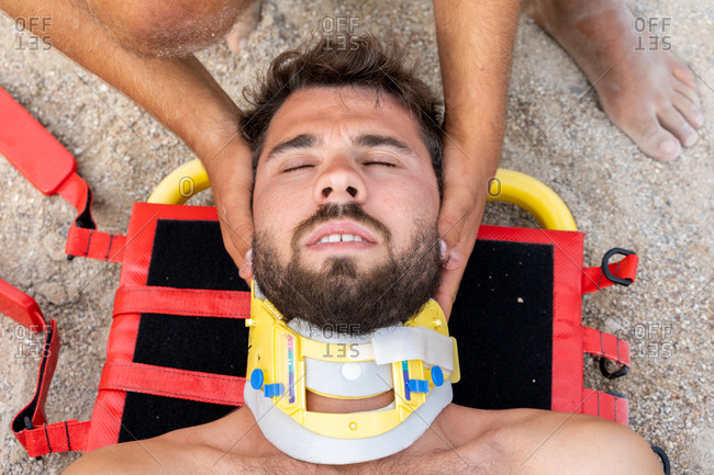 Top view of unrecognizable lifeguard in uniform helping bearded patient in emergency head block during practice at work