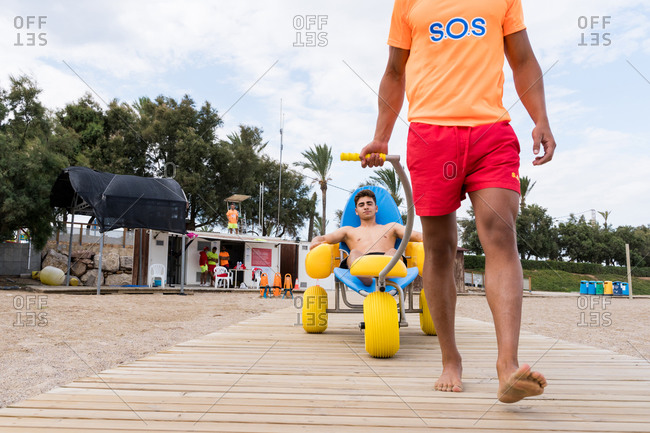 Unrecognizable lifeguard carrying bright water wheelchair with partner while having fun on sandy beach near wavy ocean