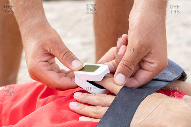 Crop unrecognizable male employee putting pulse rate meter on finger of patient on shore