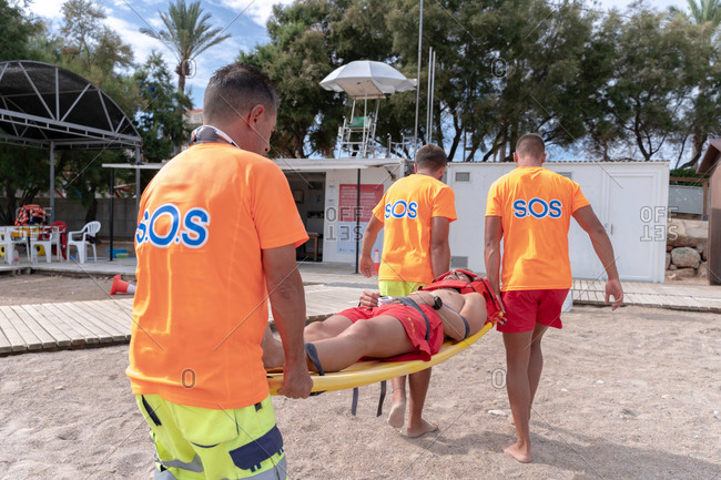 Back view of crop anonymous lifeguards in uniform carrying stretcher with lying man during training on sandy sea shore