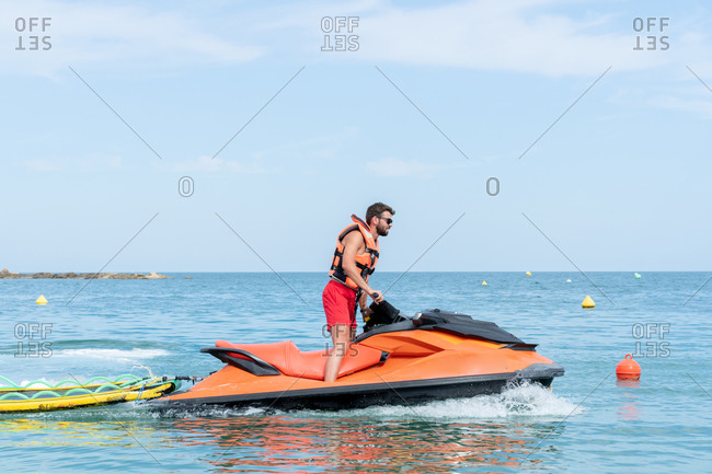 Side view of unrecognizable male worker in life jacket and shorts on bright motor boat on sea under sky