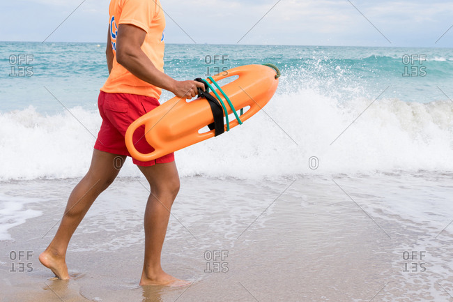 Side view of cropped unrecognizable stylish male employee with torpedo rescue buoy strolling on foamy sea under cloudy sky
